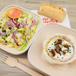 Plat camembert rôti accompagné de salade verte, pommes de terre, oignon rouges et petit pain
